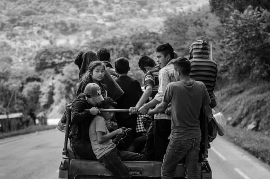 Migrant families squeeze onto vehicles to get a ride to the next town on their journey as they leave San Pedro Sula, Honduras