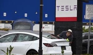 A Tesla employee cleans a car outside a Tesla showroom in Burbank, California, 24 March 2020.