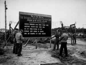 Soldiers stand before a sign at the site of the Bergen-Belsen concentration camp, which was burnt to the ground to combat the spread of typhus.