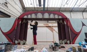 Scenic artist Joe Browne paints part for the set for The Grinning Man.