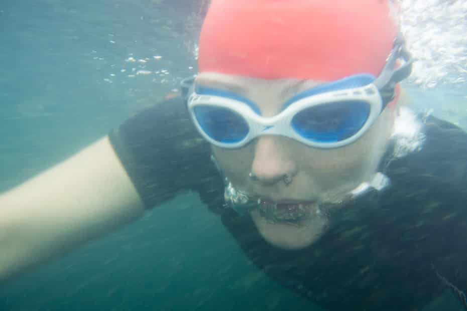 An underwater image of Teri in goggles and a red swimming cap