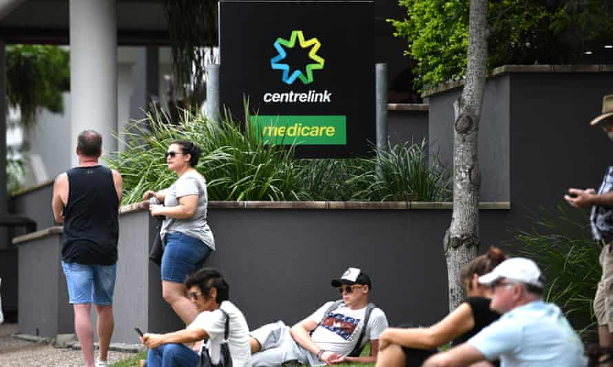 People are seen in long queues outside Centrelink office