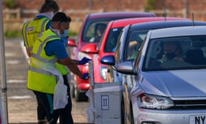 A queue of cars with people in hi-vis jackets handing tests to drivers