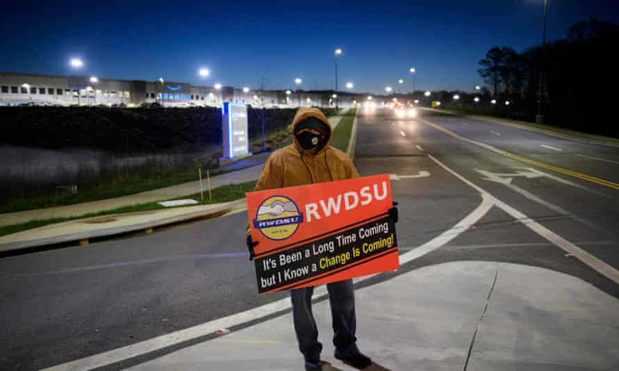 A union supporter stands before sunrise outside the Amazon fulfillment center in Bessemer, Alabama, in March.