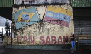 A Venezuelan woman stands by a mural of the Brazilian and Venezuelan flags in Pacariama, Brazil, on 27 June.