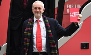 Britain's Labour Party leader Jeremy Corbyn holds up a copy of their general election manifesto as he arrives for a manifesto launch event in Birmingham, northwest England.