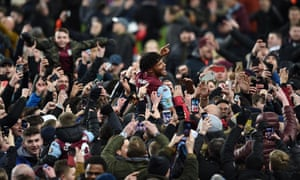 Aston Villa defender Tyrone Mings is lifted by fans celebrating their team reaching the Carabao Cup final