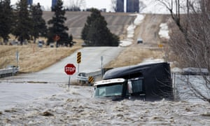 A semi truck and trailer are swept off the road by floodwaters in Arlington, Nebraska.