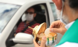 A priest offers communion to a Catholic devotee during a drive-in mass celebrated in a parking lot due to the pandemic, in Bogota. A decree issued by the Colombian government on March 22 extended the prohibition of celebrating religious gatherings across the country until August 31.