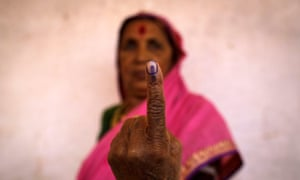 A woman shows her ink-marked finger after voting inside a polling station in Maharashtra in 2014