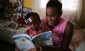 In Belize City, a book is read to three-year-old Alishia