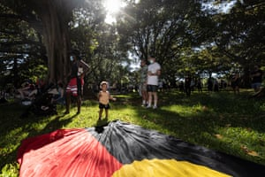 A young child standing next to the Aboriginal flag during the rally in Sydney.