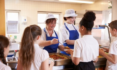 Two women serving kids food in a school cafeteria, back view