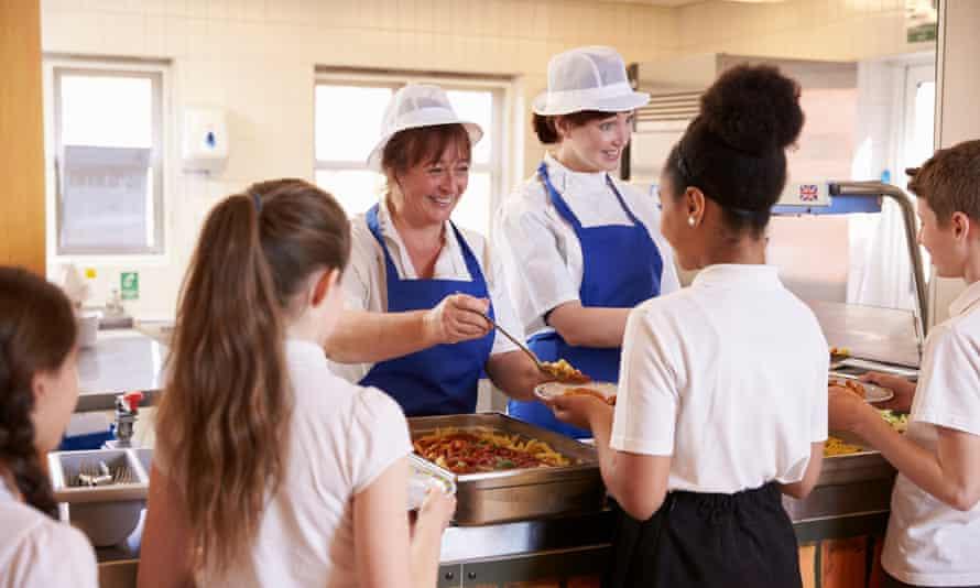 Dinner ladies serving children in a school cafeteria