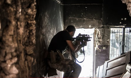 An Iraqi soldier fires at an Isis militant in Mosul, Iraq.
