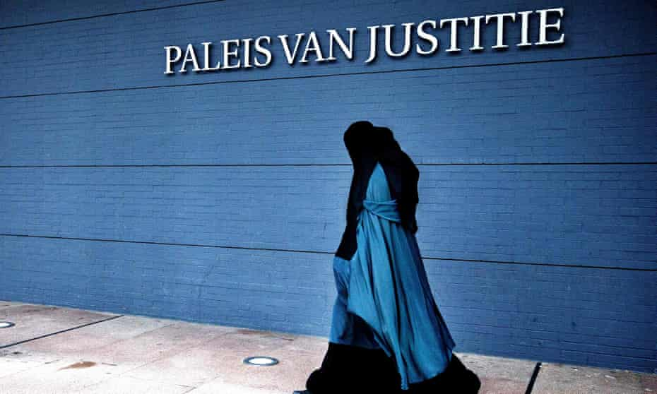 A woman wearing a burqa walks past the Palace of Justice in the Hague