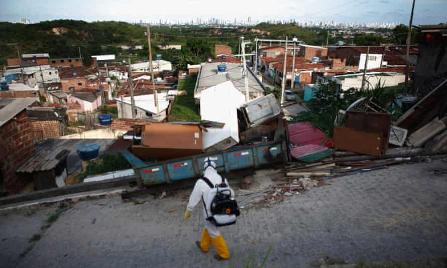 A city worker fumigates for mosquitoes in a favela above Recife.