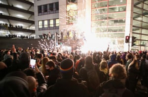 Demonstrators launch fireworks at police officers.