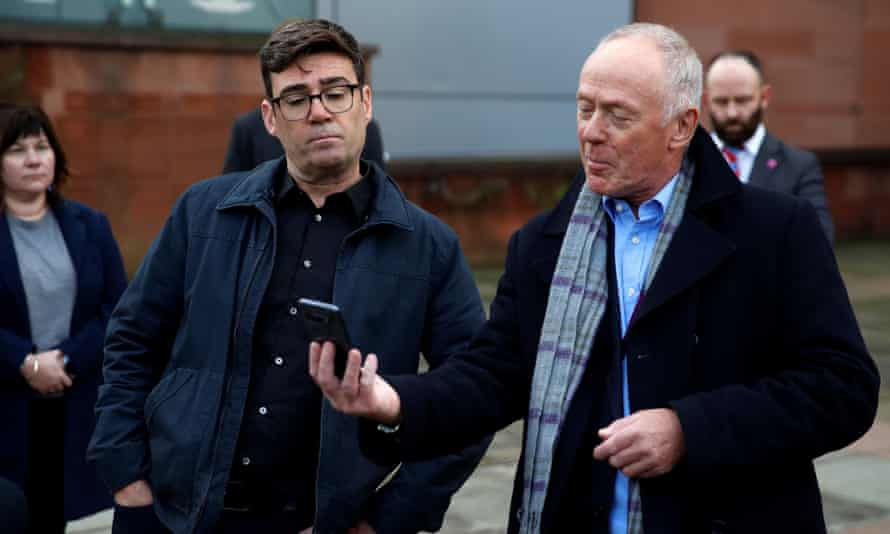 Reading a text update with deputy mayor and leader of Manchester city council, Sir Richard Leese, during a press conference last month following the breakdown of Covid talks with the government.