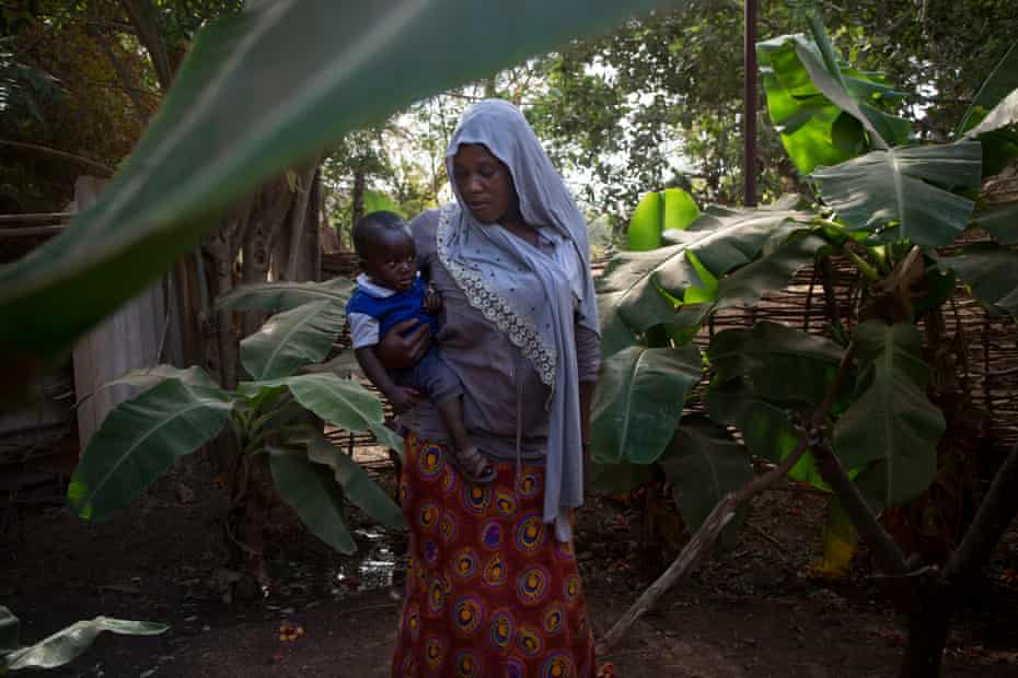 Holding her 11-month-old son, Ibrahim, Fatou Ceesay, 33, walks in the garden outside her home to her office in central Gambia