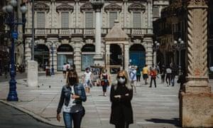 People walk in Verona, Italy.