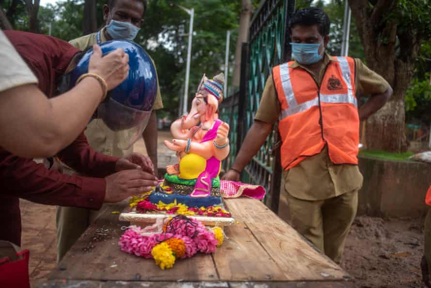 Devotees pay tribute, remove ornaments and pray to the statue of Lord Ganesh before it is taken by workers to be immersed in the artificial pond.