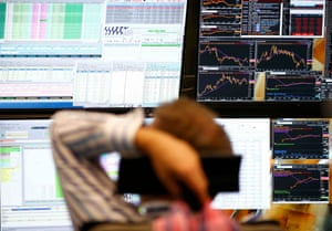 A trader sits in front of the computer screens at his desk at the Frankfurt stock exchange.