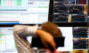 A trader sits in front of computer screens. The FTSE 100 index in London plunged almost 9% and fell through 6,000 points when trading began on Monday morning.