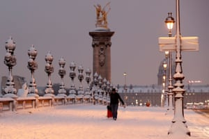 A man crosses the Pont Alexandre III Bridge in the early morning