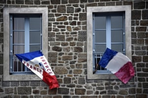 A picture taken on November 27, 2015, shows French national flags put on a window in Hede-Bazouges, north of Rennes, during the National Tribute to the 130 people killed in the November 13 Paris attacks.