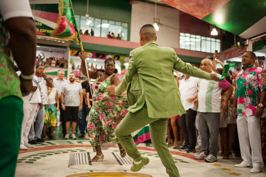 The Mangueira samba school flag-bearer and her escort perform during a rehearsal show.