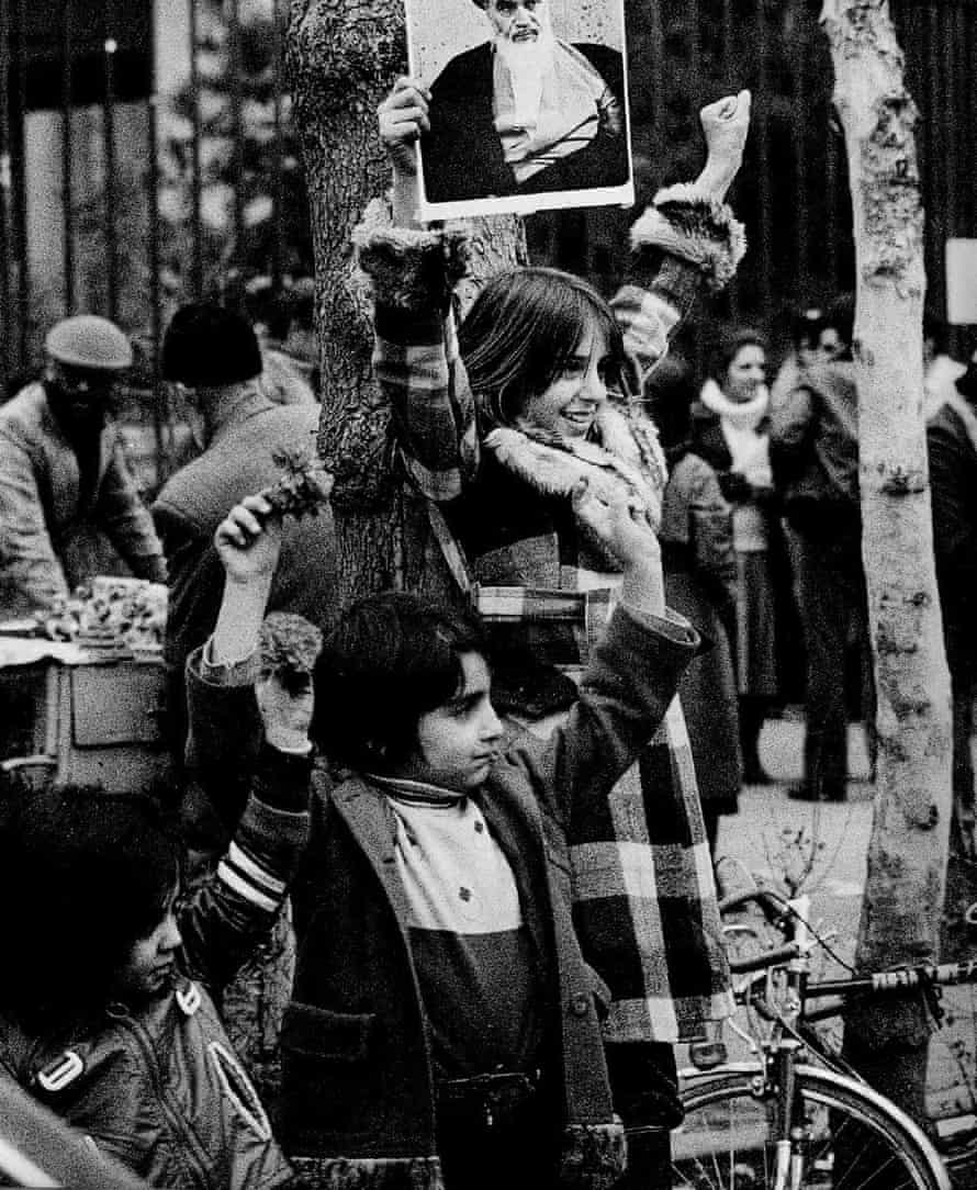 A young girl holds up a photo of Ayatollah Khomeini above her head.