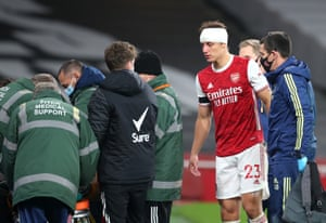 Luiz of Arsenal looks on Jimenez receives treatment