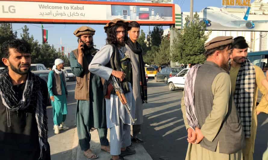 Taliban fighters stand outside Hamid Karzai International Airport in Kabul