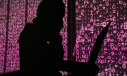 A silhouette of a man in a balaclava sitting at a laptop.
