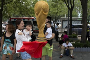 A child looks at a replica of the World Cup trophy made from human hair