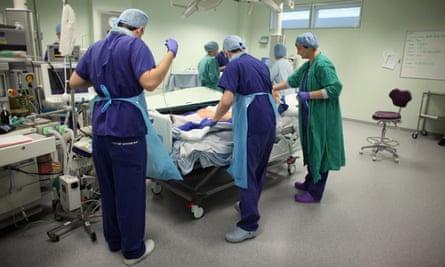 Operating theatre staff care for a patient