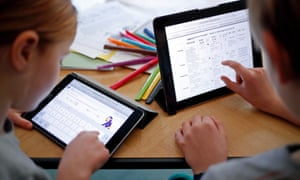 Children use iPads to complete online schoolwork at home