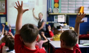 Children at school raising their hands to answer a question.
