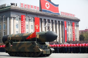 People cheer as a missile is driven past during a military parade in Pyongyang