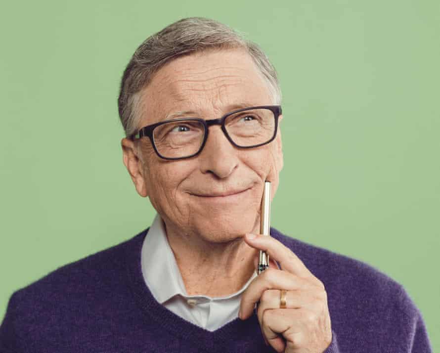 Bill Gates wearing a purple jumper against a green wall