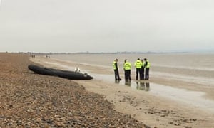 Police and Border Force agents near a empty dinghy on the beach at Lydd-on-Sea in Kent after a group of people were detained.