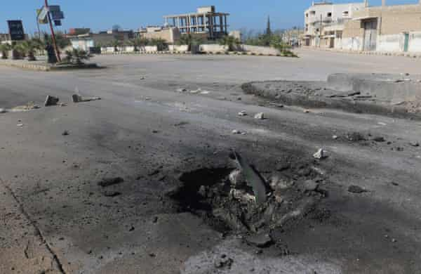 A crater is seen at the site of an airstrike.