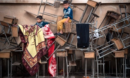 Syrian children sit on classroom tables at a school turned into a shelter for displaced people in Hasakeh, north-east Syria