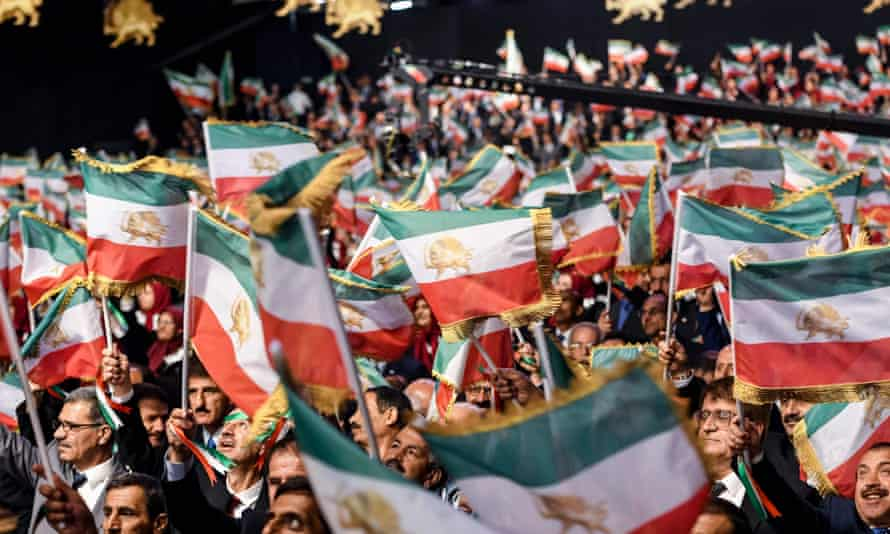Mujahedin-e-Khalq members wave Iranian flags at the annual conference in their compound in Albania.