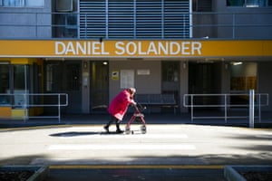 A woman pushes her walking frame past the Daniel Solander building