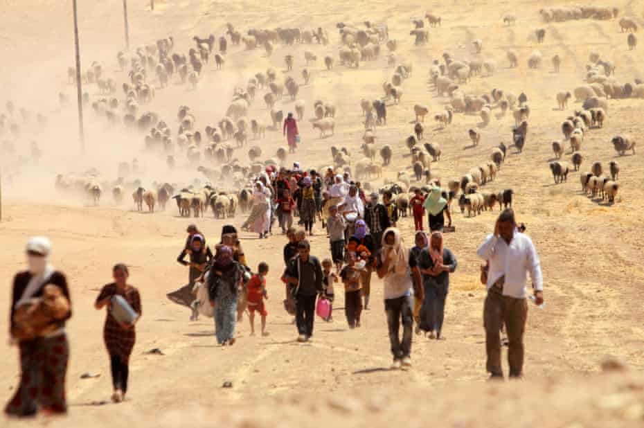 Displaced people from the minority Yazidi sect, fleeing violence from forces loyal to Isis in Sinjar town, walk towards the Syrian border, on the outskirts of Sinjar mountain, 10 August 2014.
