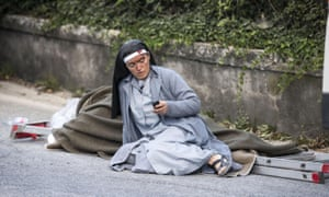 A nun checks her mobile phone following the earthquake in Amatrice