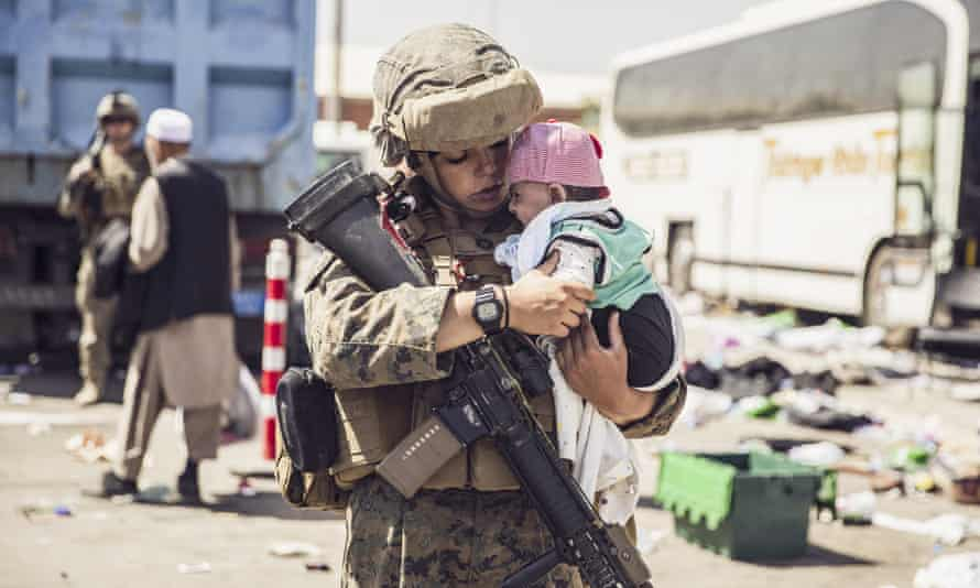 A Marine with the 24th Marine Expeditionary Unit carries a baby as the family processes through the evacuation control center in Kabul.