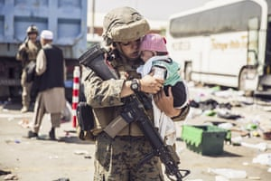 Kabul, Afghanistan: a US marine carries a baby as its family wait to be evacuated from Hamid Karzai international airport